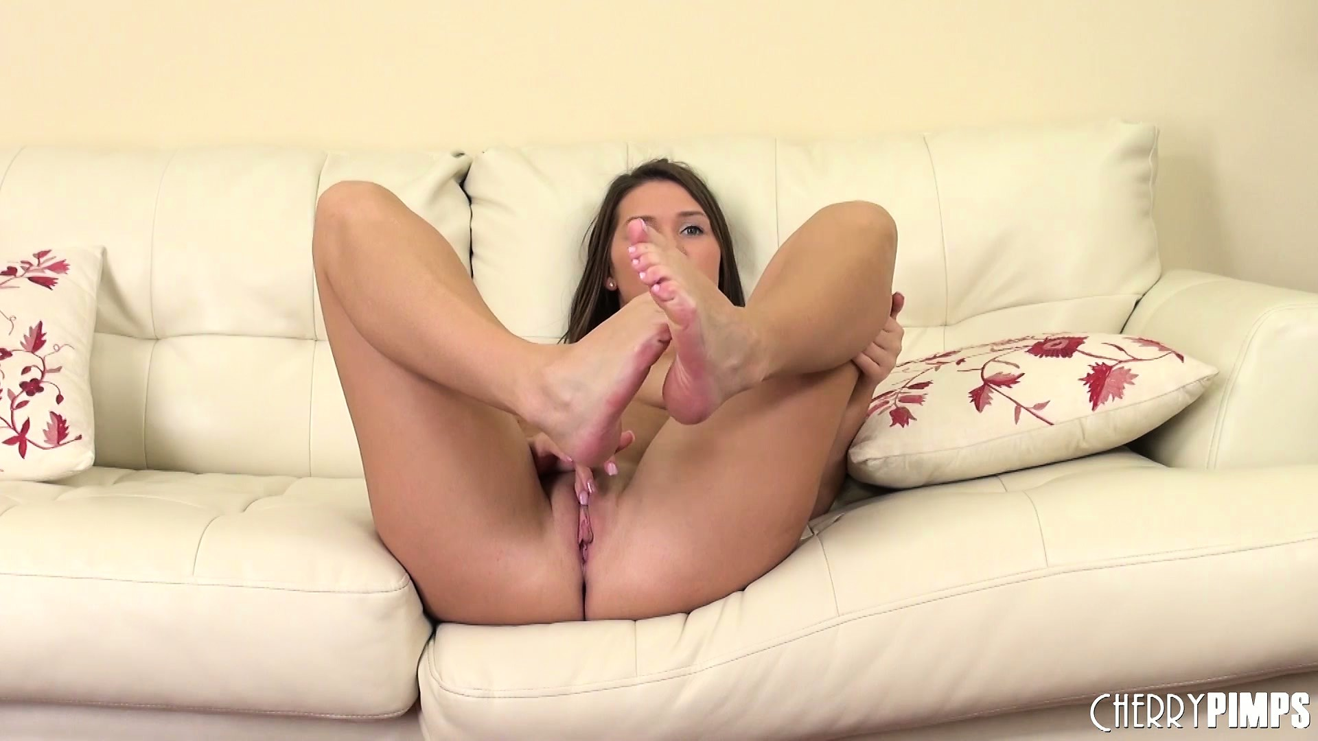 Porn Tube of The Cute Babe Sits On The Couch With A Vibrator Working Its Magic Between Her Legs